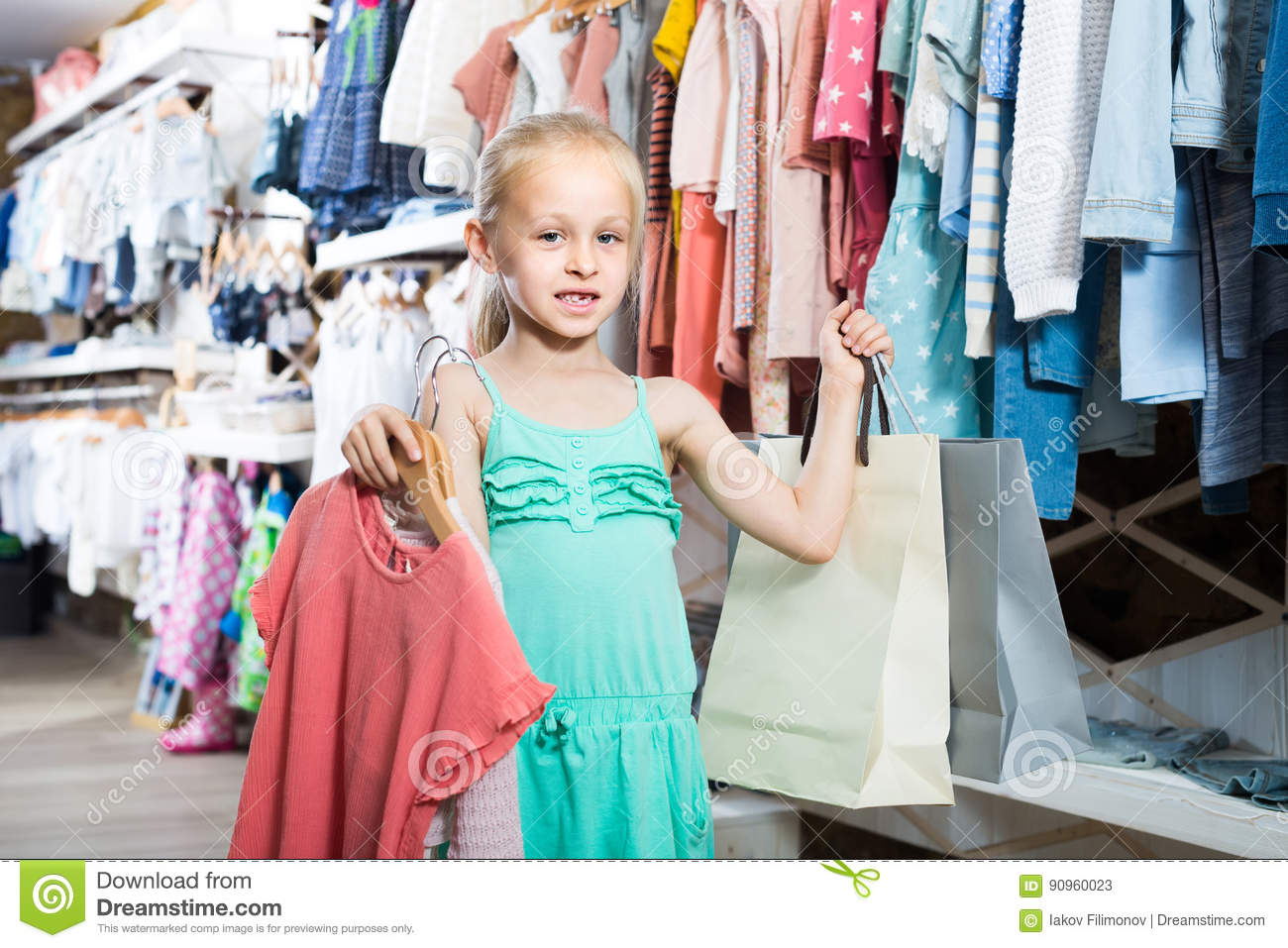 0ad8ae76b Portrait of cheerful american girl standing in kids clothes store with  shopping bags