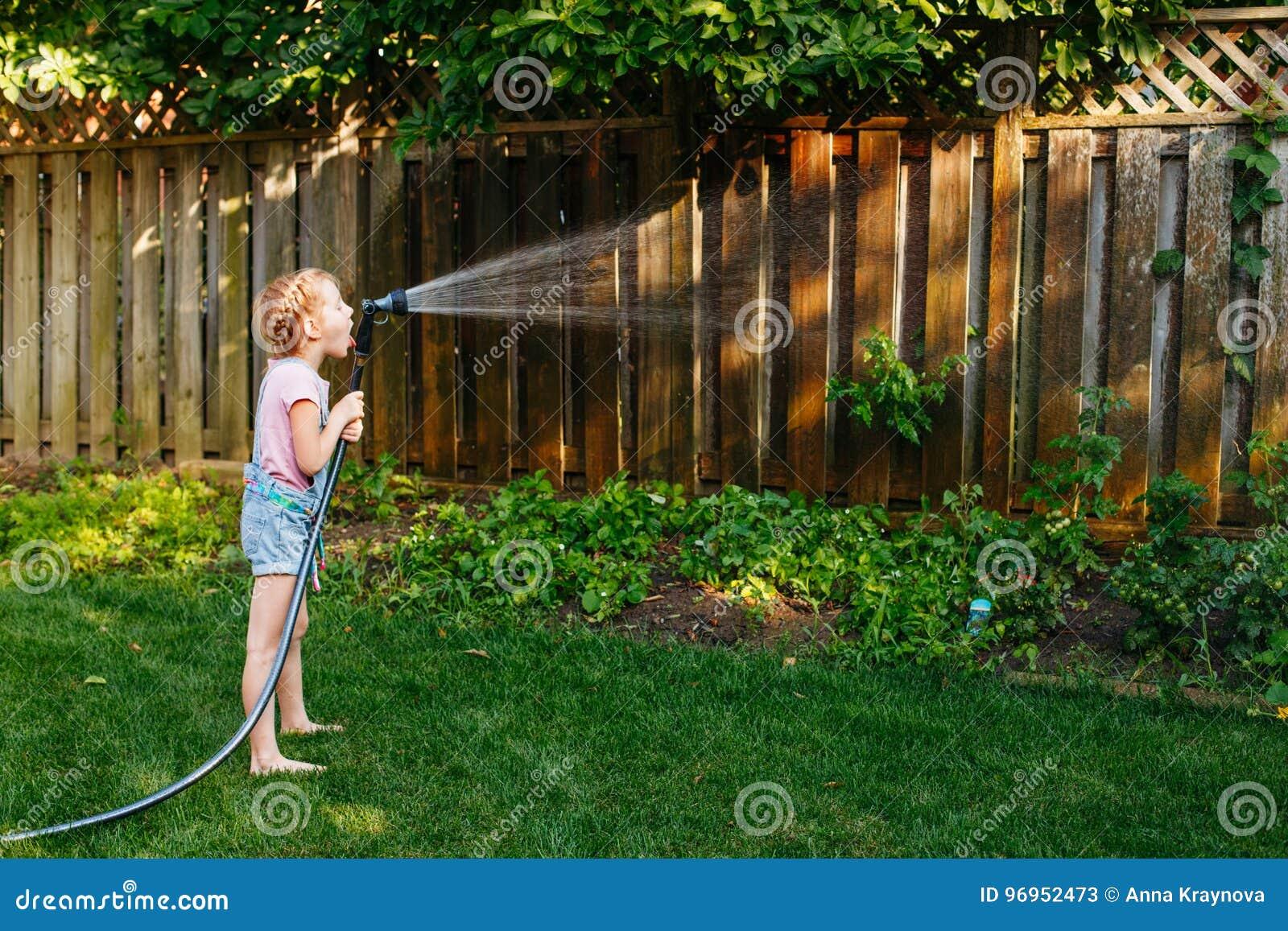 Little Girl Watering Green Plants On Backyard Stock Image - Image of ...