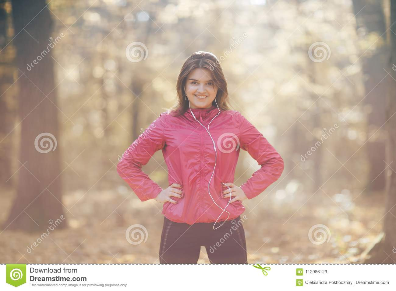 Portrait of a girl who trains and listens to music in the morning autumn park