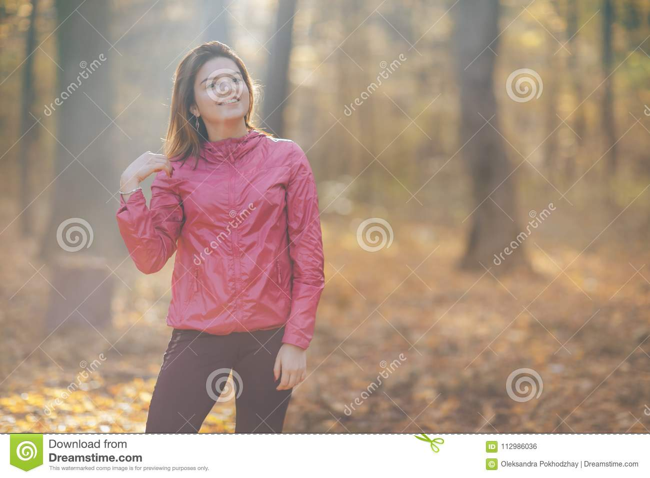 Portrait of a girl who trains in the morning autumn park. Good morning light