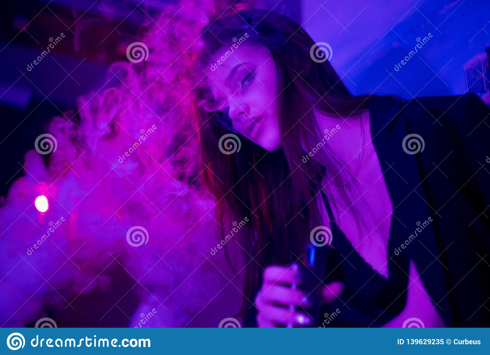 Portrait of glamour seductive gorgeous brunette woman smoking electronic cigarette in neon color light in studio