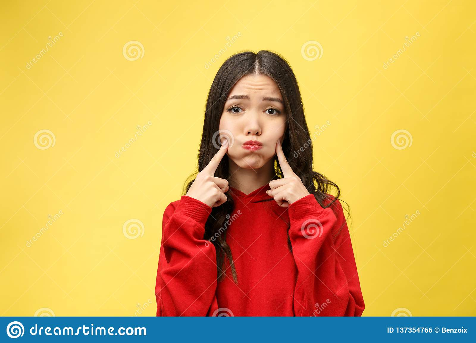 Portrait of good looking young attractive woman has curious gaze at camera, keeps finger on chin, listens attentively