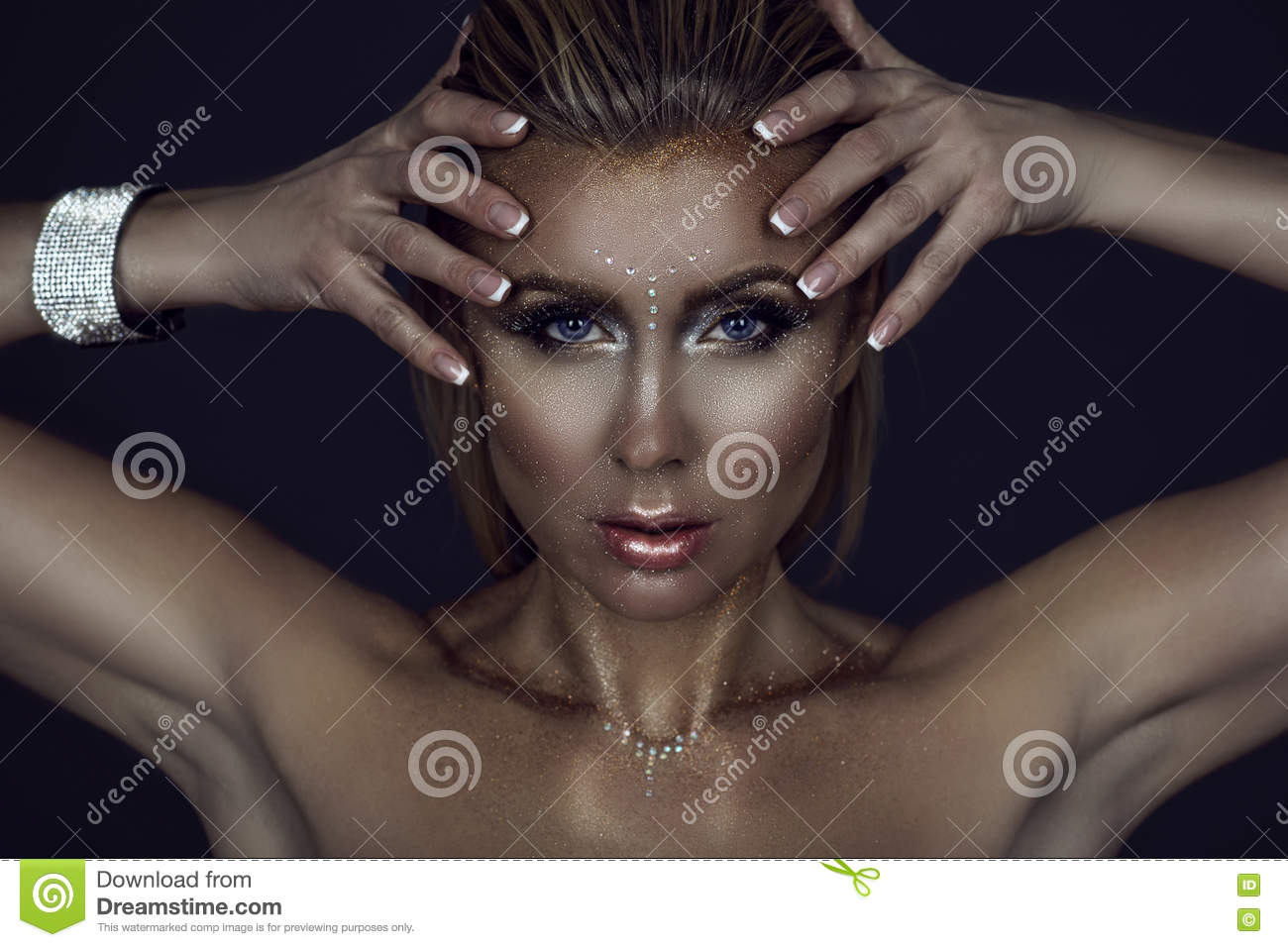 Portrait of gorgeous blond woman with wet hair and glittering artistic make up holding her hands close to the face