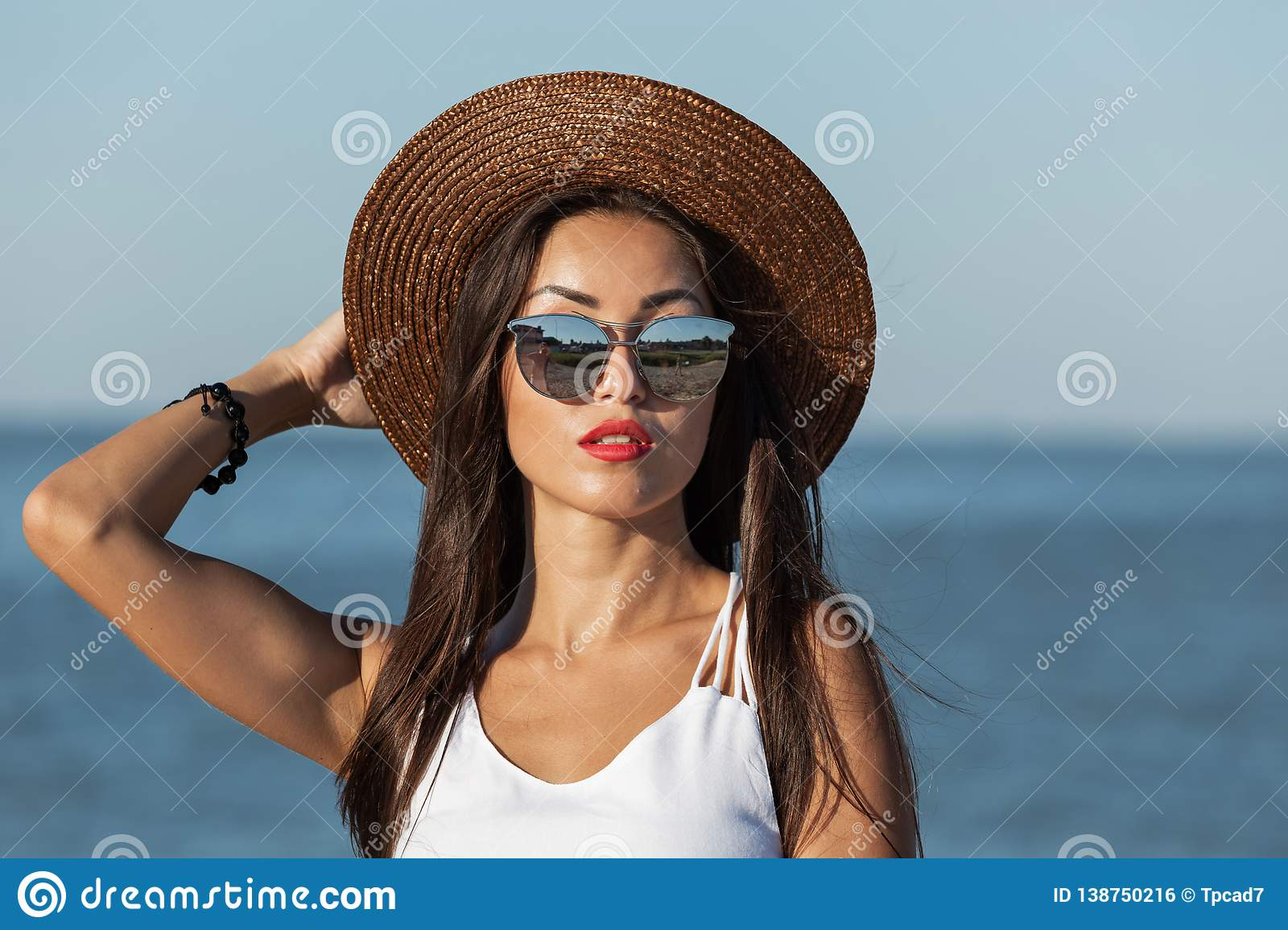 Portrait of a gorgeous brunette girl with long hair and red lipstick in white dress, sunglasses and brown hat near the