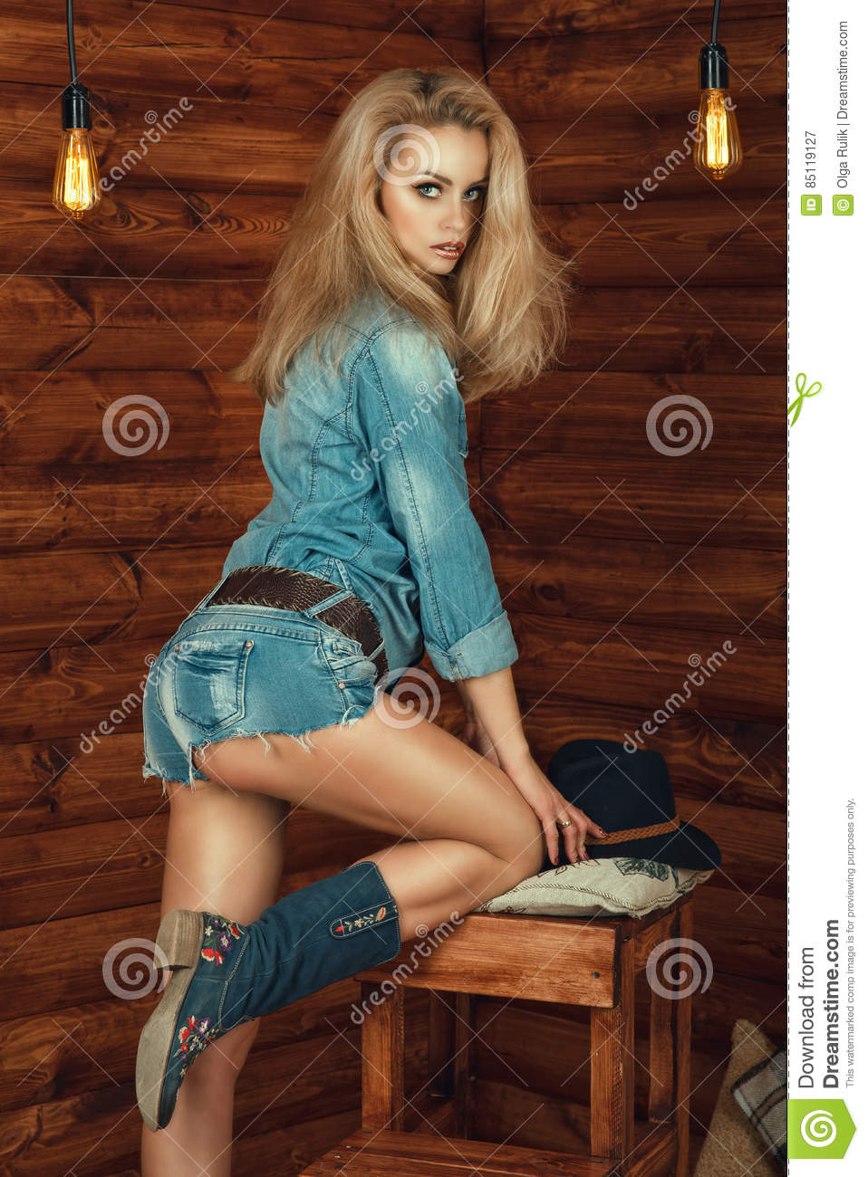 Portrait of gorgeous blond wearing denim shirt, jeans pants and suede boots with floral embroidery
