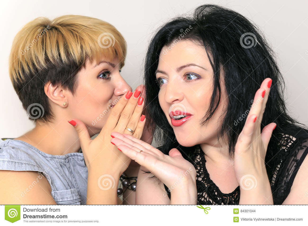 Portrait of a gossip girl telling a secret in the ear to her friend sitting on a couch at home