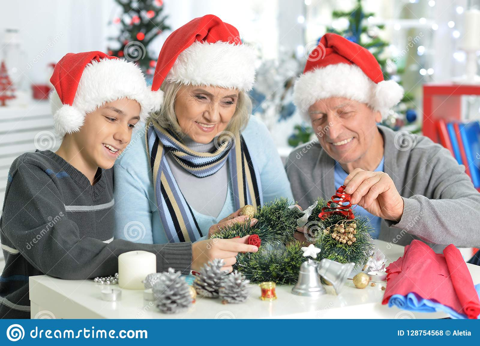 Portrait of grandparents with boy preparing for Christmas