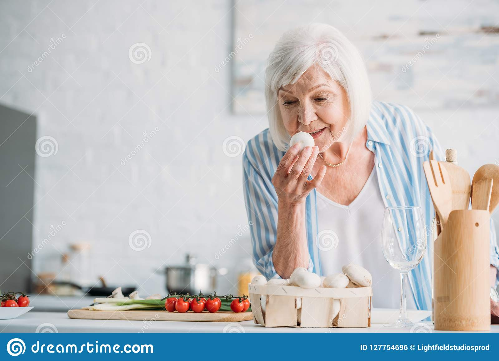 portrait of grey hair lady checking mushrooms while cooking dinner at counter
