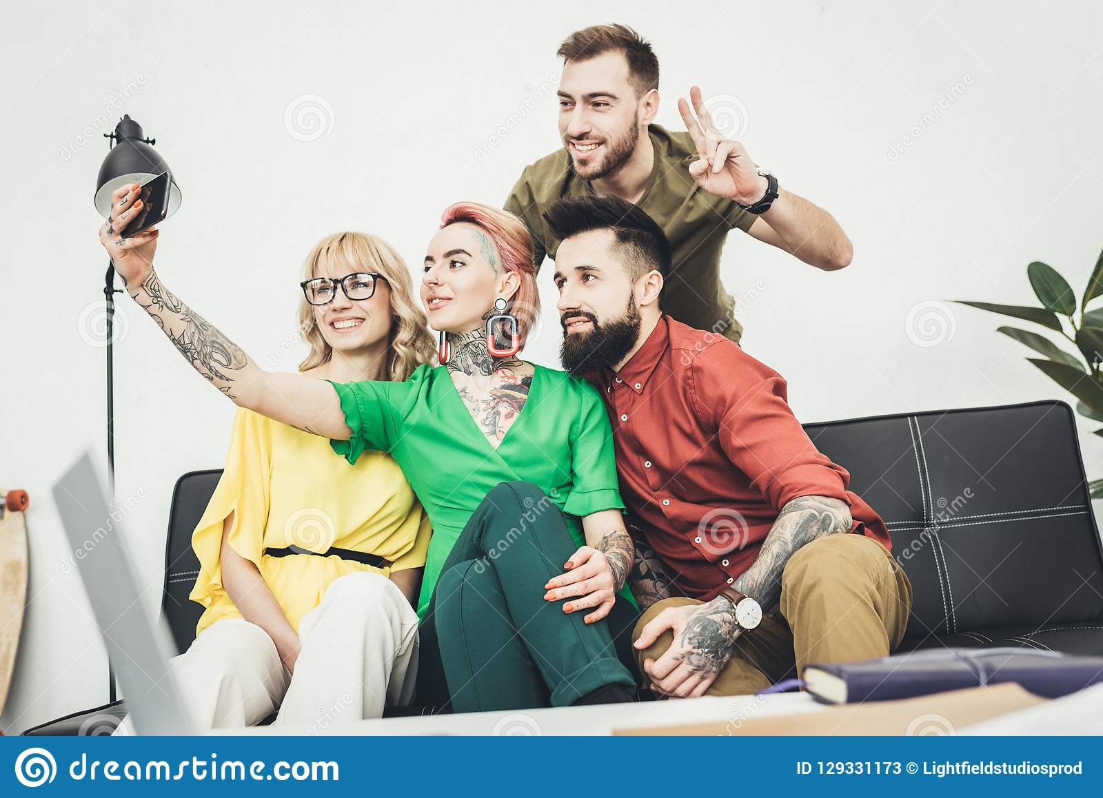 Portrait of group of creative workers taking selfie on smartphone together stock photos