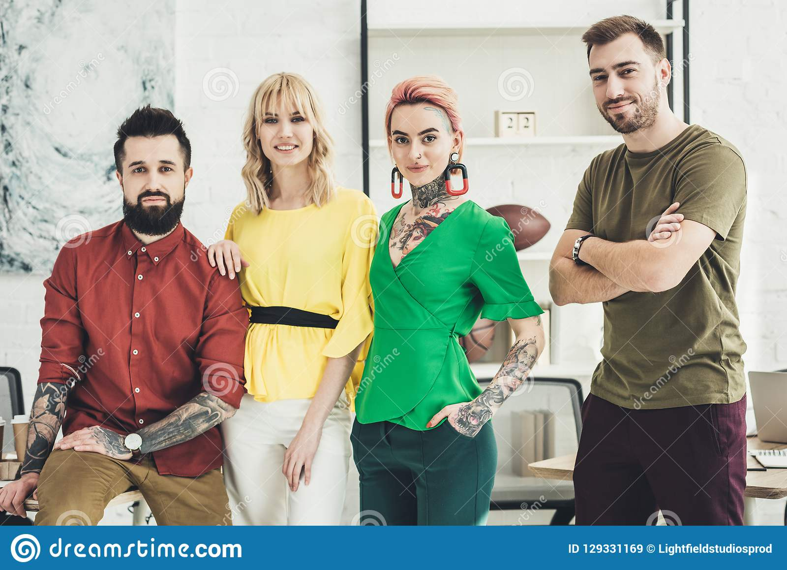 Portrait of group of young stylish creative workers looking at camera in office royalty free stock images