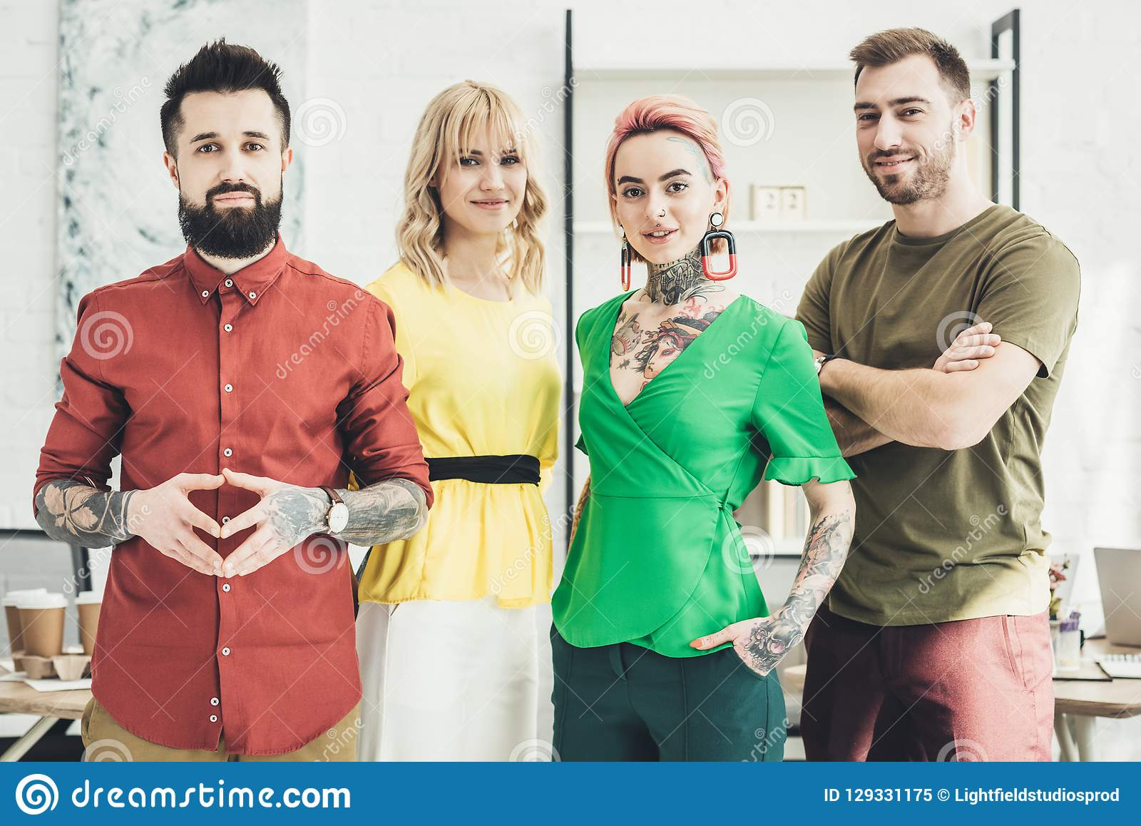 Portrait of group of young stylish creative workers looking at camera in office royalty free stock photo
