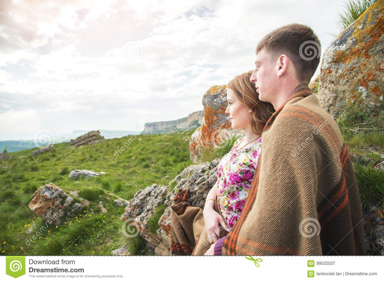 Portrait of a guy with a girl covered in a blanket standing in an embrace in nature and smiling with happiness