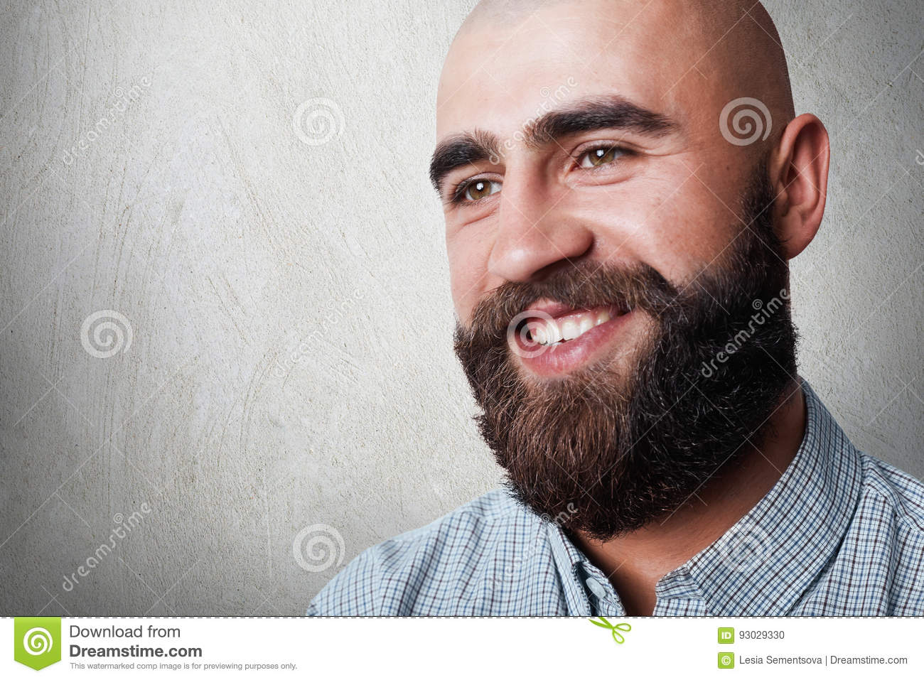 A portrait of handsome bald man with thick beard and mustache having sincere smile while posing against white background. A fashio