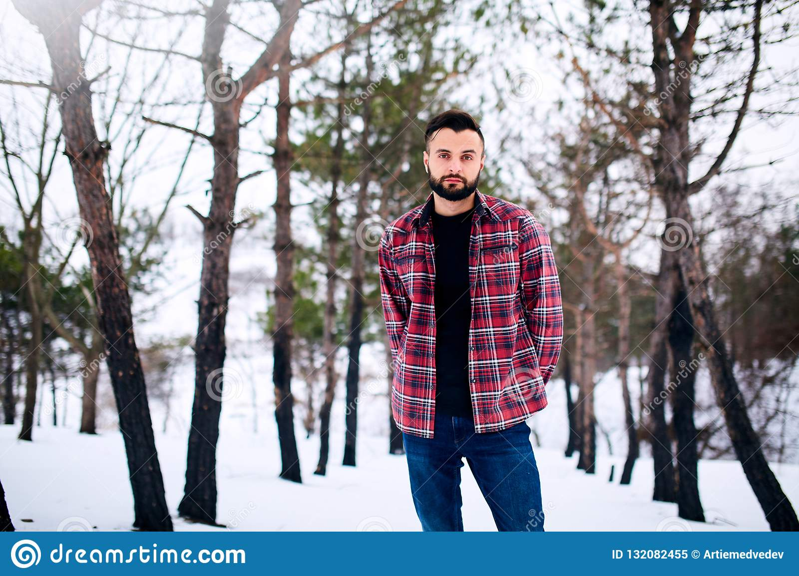 6d013ead53 Portrait of handsome bearded young man in red hat and checkered shirt in  winter village near forest