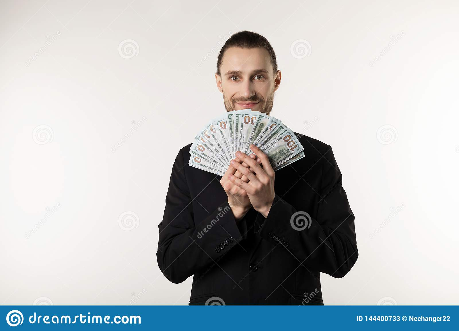 Portrait of handsome businessman in black suit that hides his face behind the money banknotes