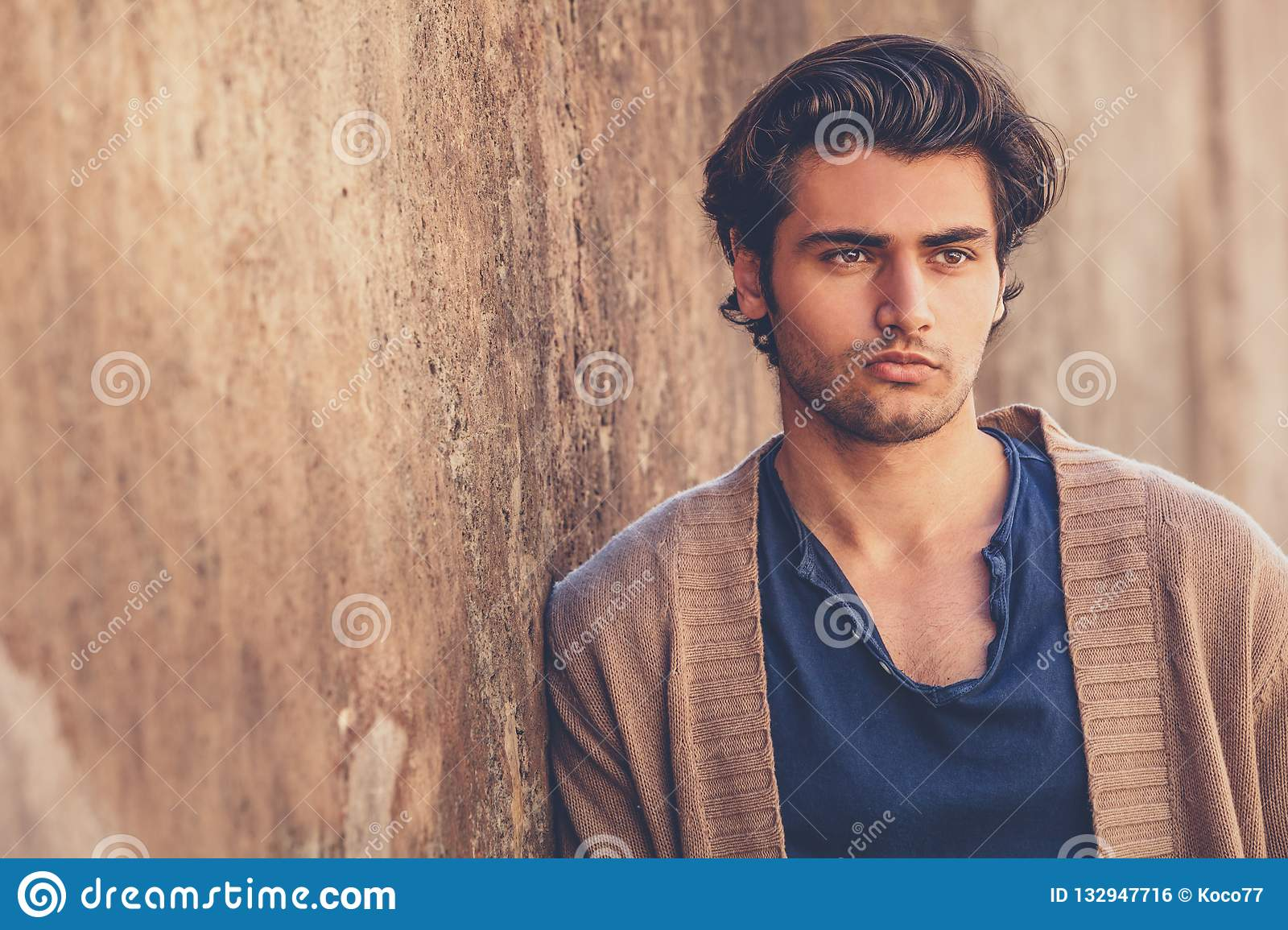 Portrait of handsome and charming young man. He is leaning against an outdoor wall.