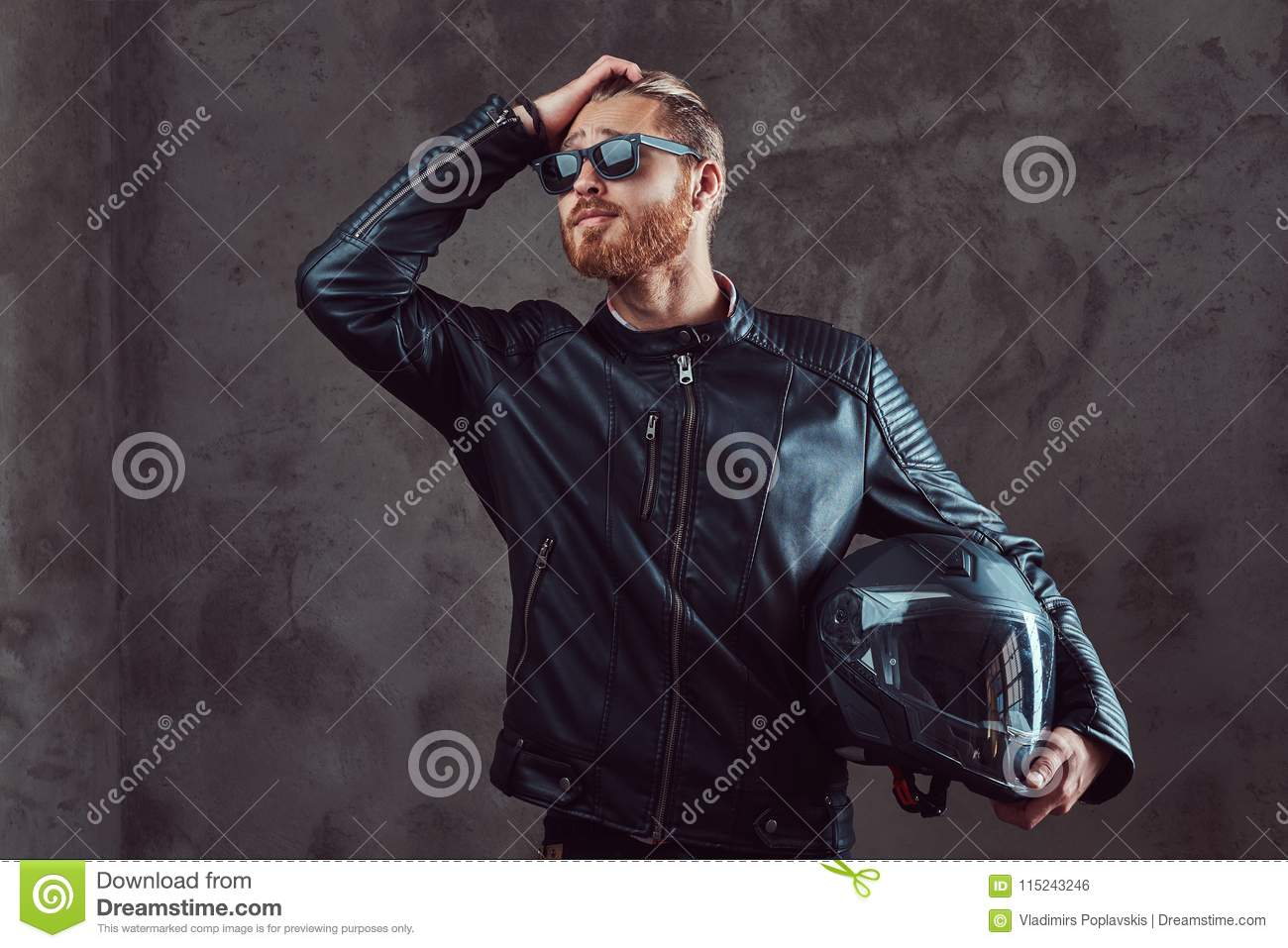 Portrait of a handsome stylish redhead biker in a black leather jacket and sunglasses, holds motorcycle helmet, posing