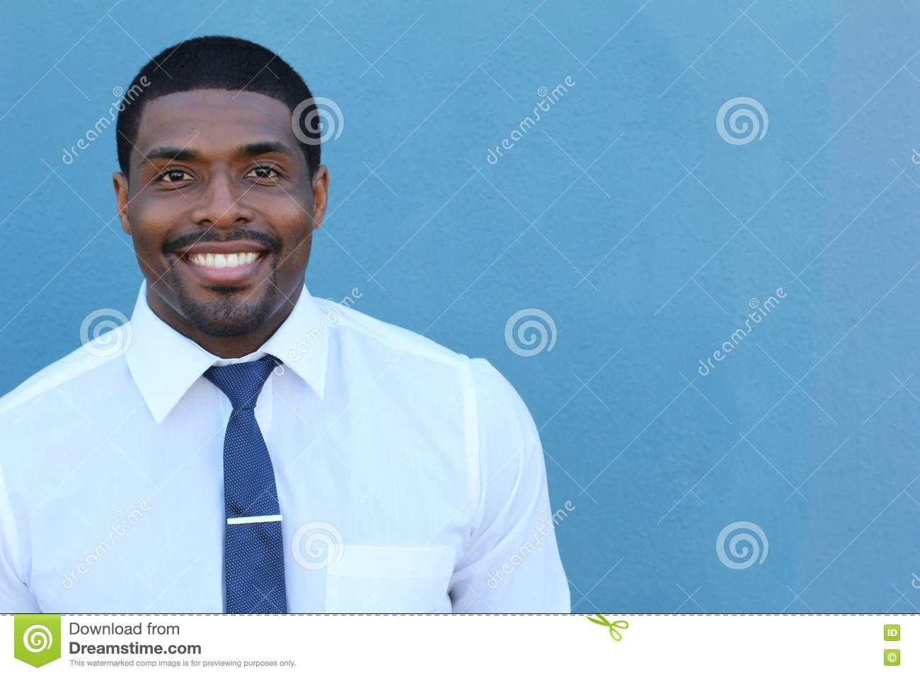 Portrait of handsome confident young African businessman standing smiling happy, looking at camera
