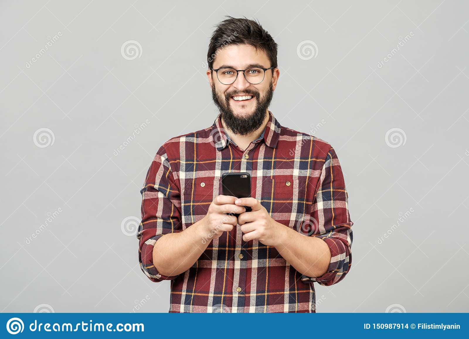 Portrait of handsome european man holding telephone while texting