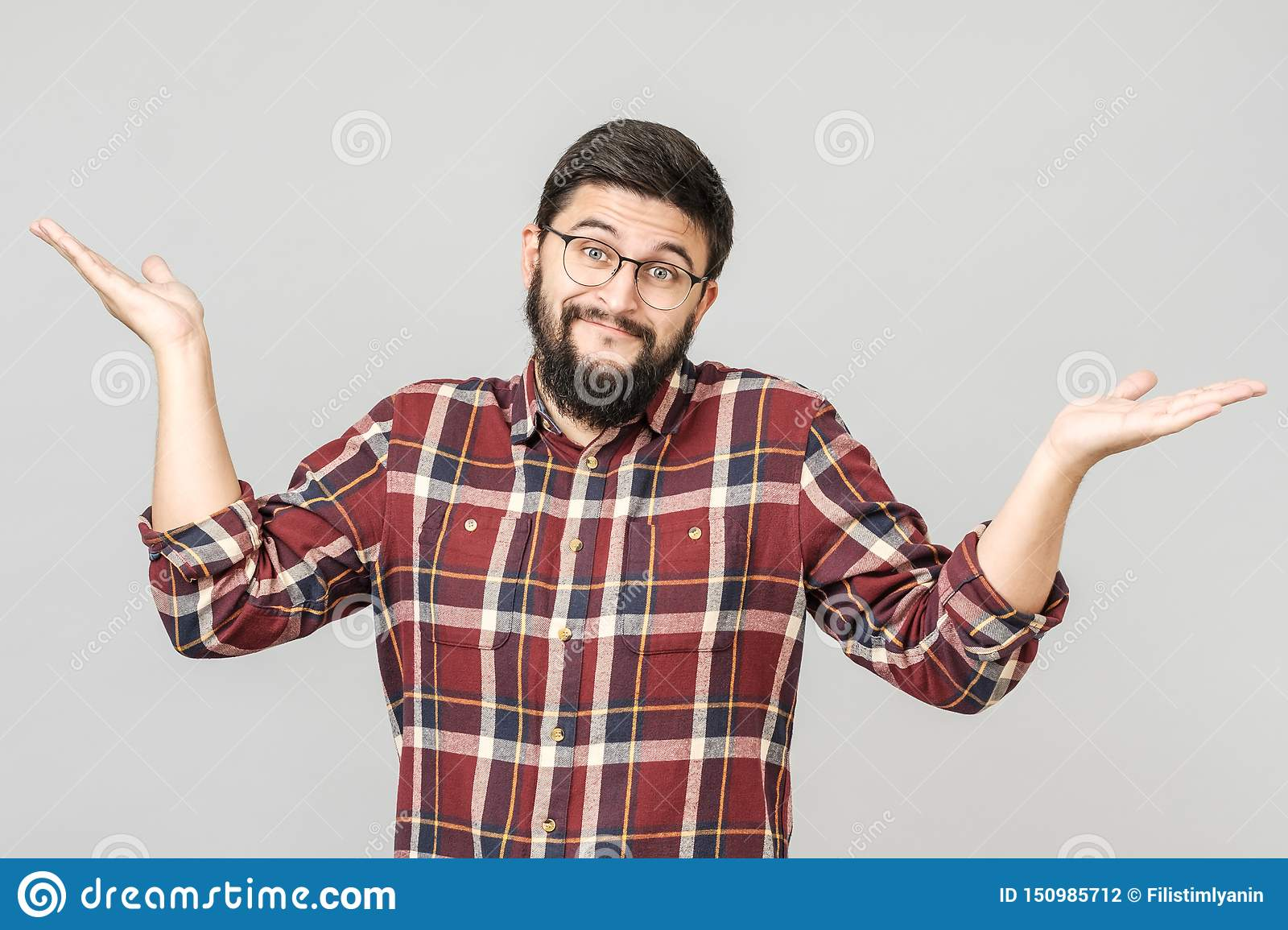 Portrait of handsome guy looking upside and shrugging his shoulders