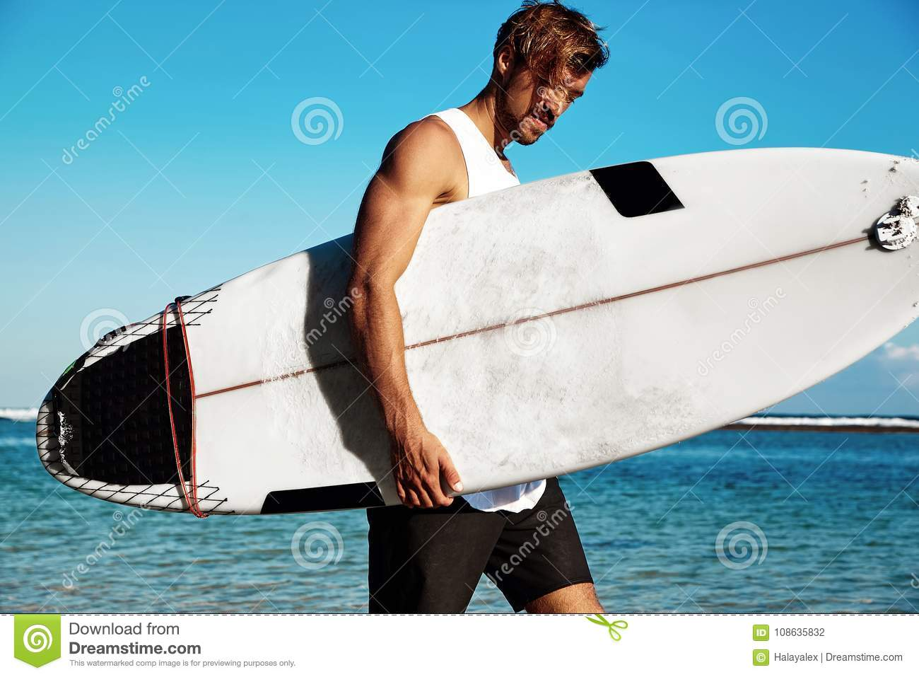 Portrait of handsome hipster sunbathed fashion man model surfer wearing  casual clothes going with surfboard on blue ocean and sky background 9d58a7da4