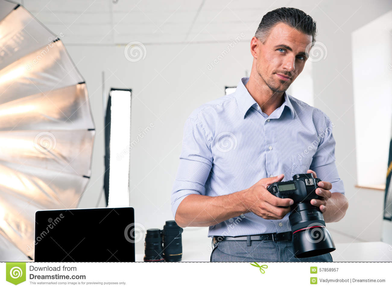 Portrait of a handsome man holding camera
