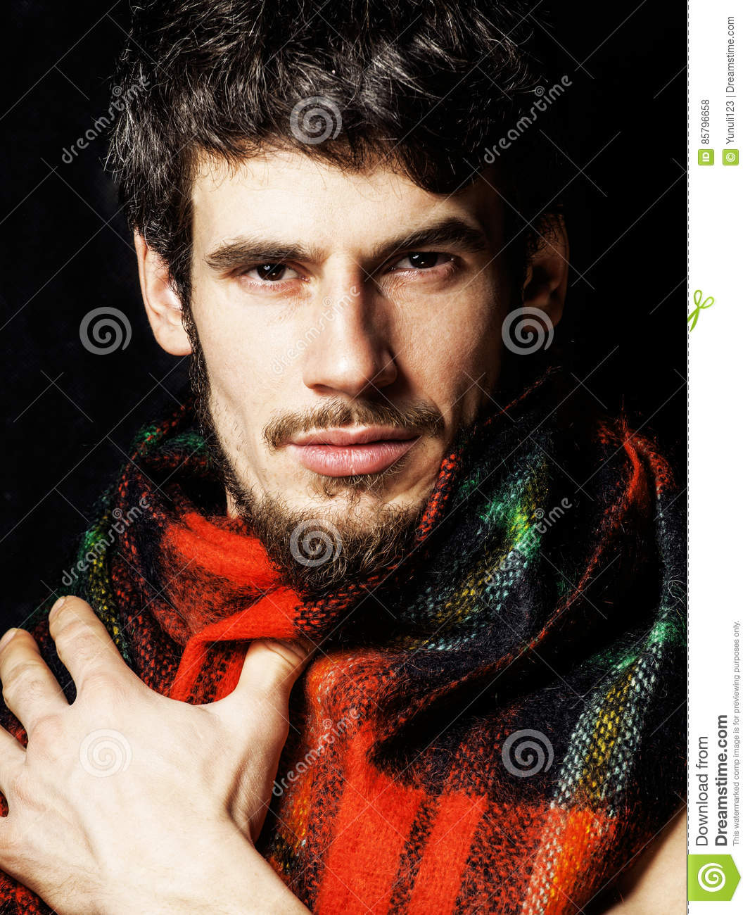 portrait of handsome man warmed up in scarf christmas colored