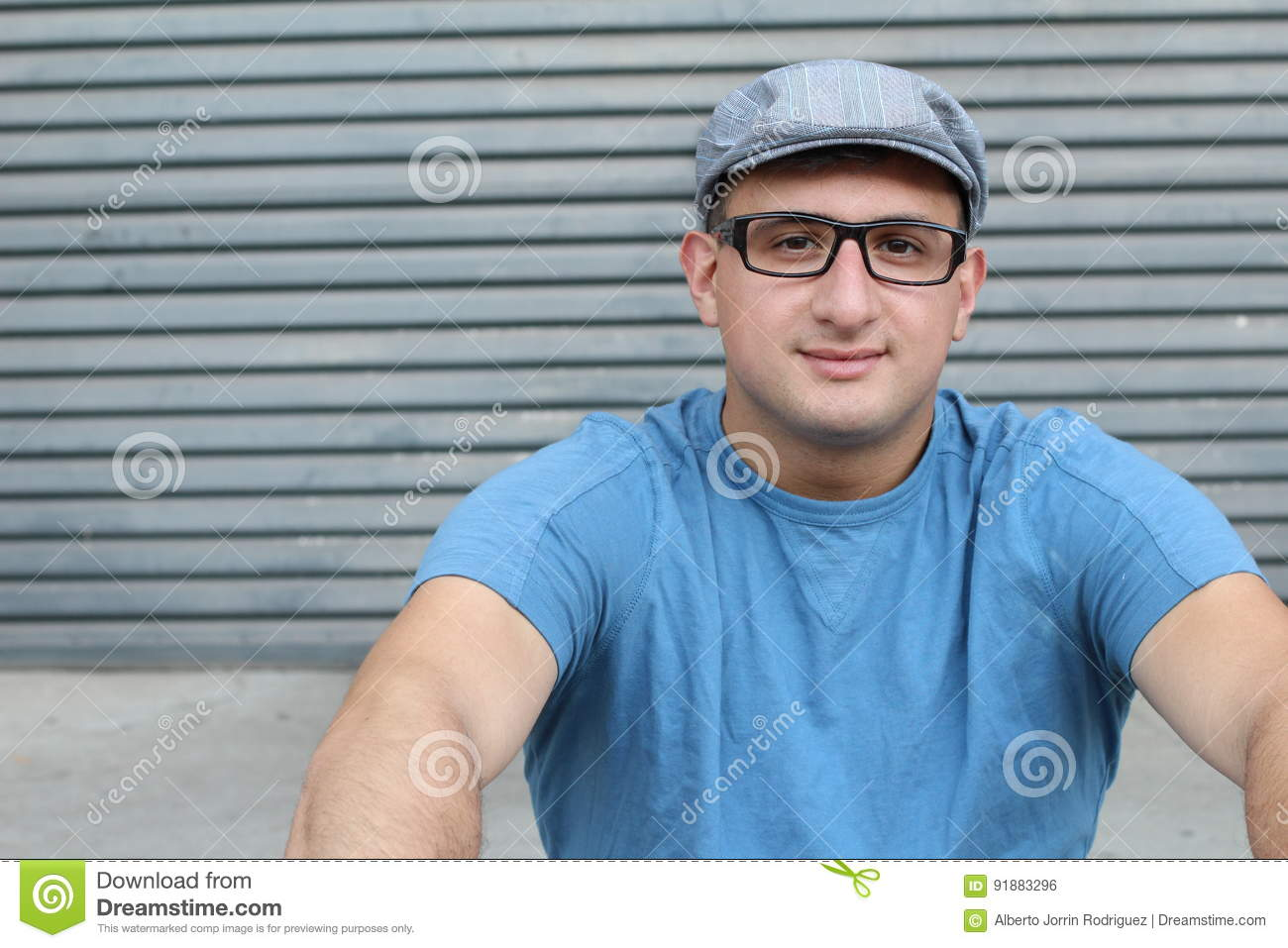 Portrait of handsome real looking man wearing glasses and hat sitting outdoors