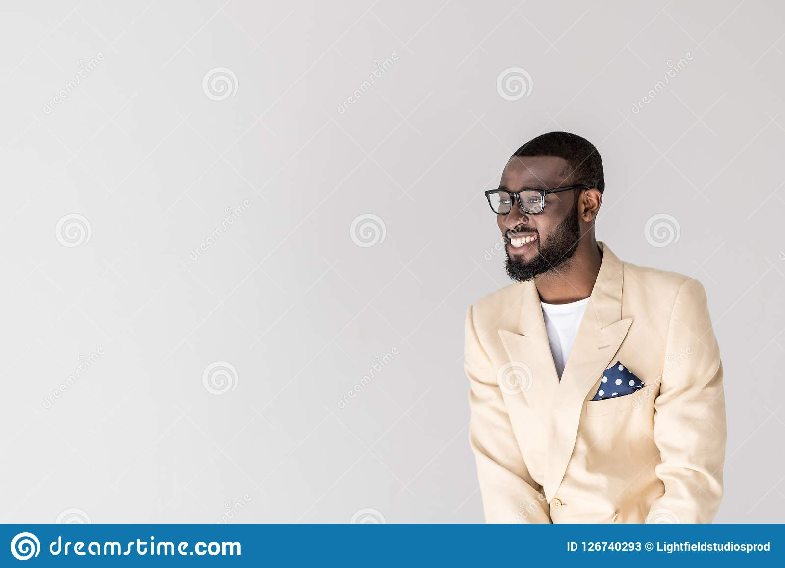 portrait of handsome young african american man in eyeglasses smiling and looking away