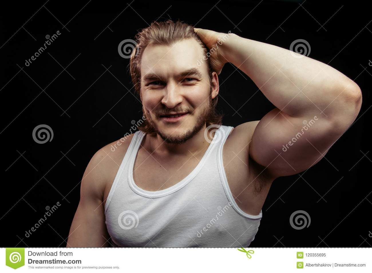 Portrait of a handsome young fair-haired man showing and his big biceps