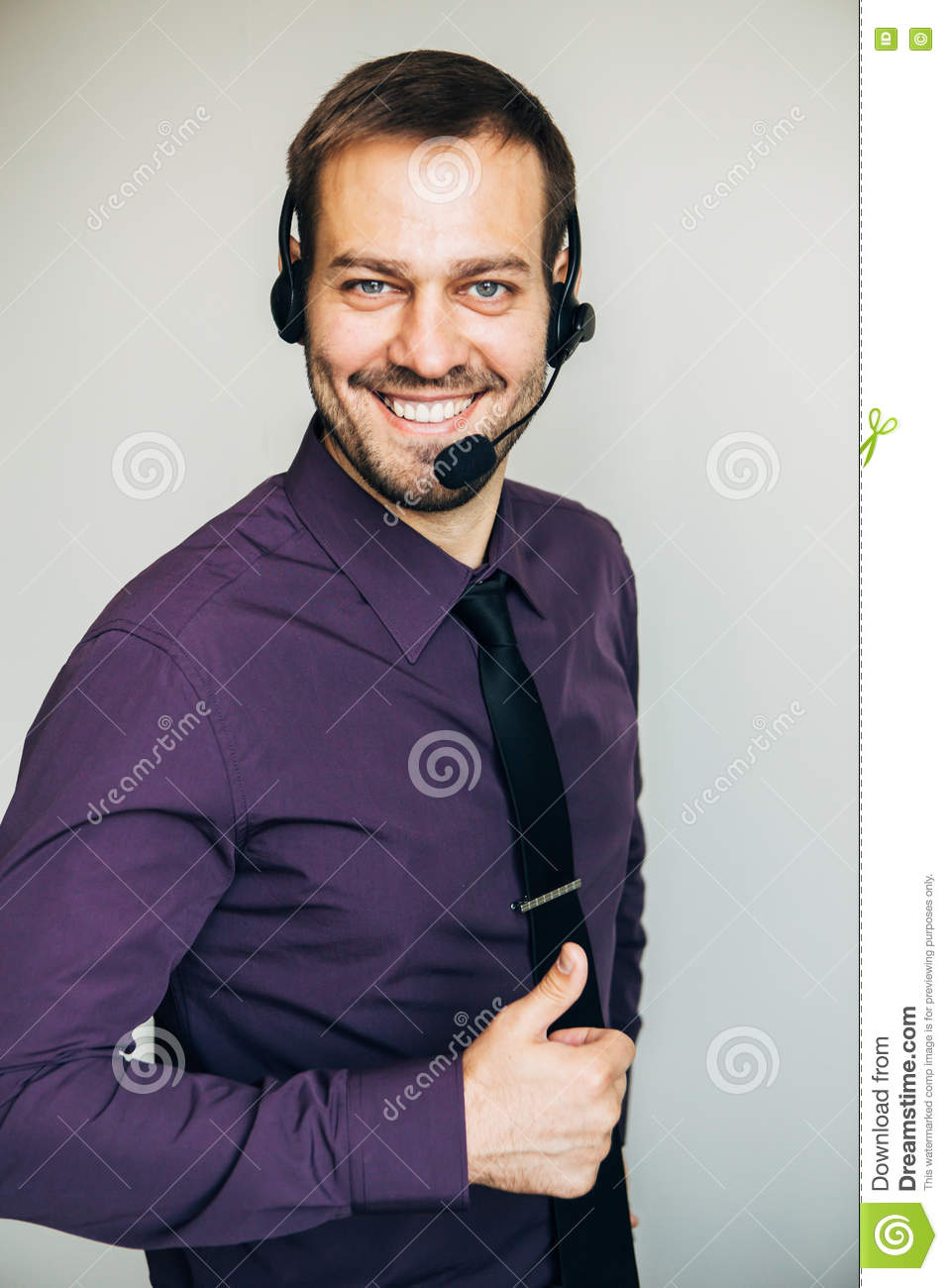 Portrait of handsome young male operator in headset looking at camera and smiling while standing against white