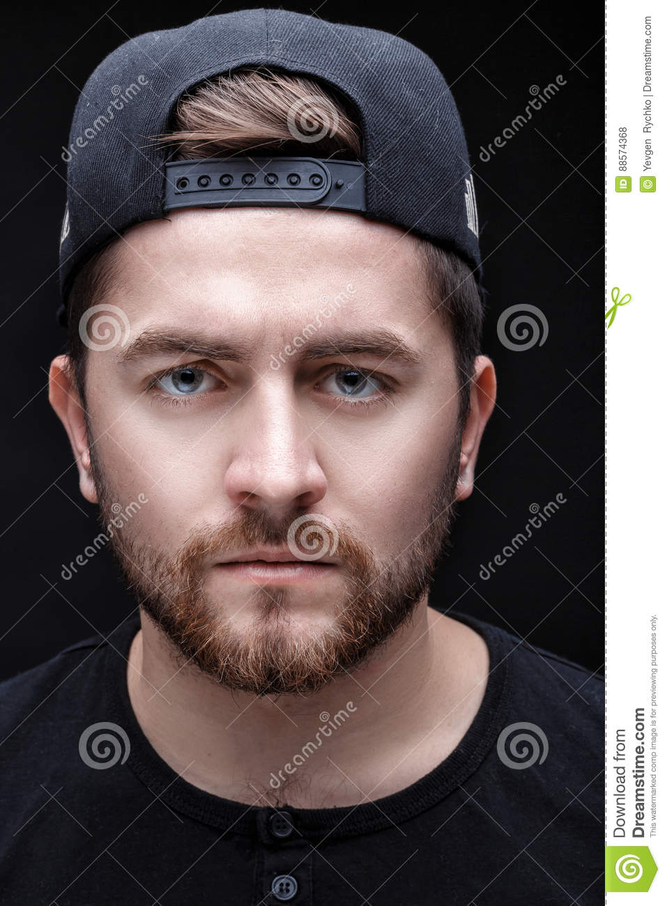 dd726cc65ca Portrait of a handsome young brunette man in a black shirt and cap on a  black background. rapper