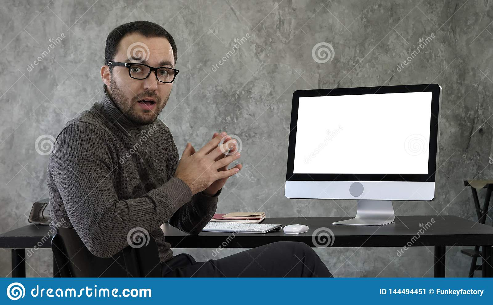 Portrait of handsome young man in casual in the office talking to the camera explaining something near the screen. White