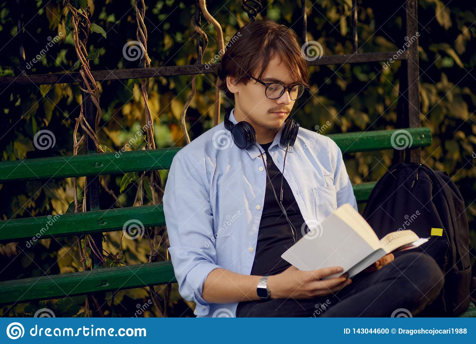 Portrait of a handsome young man in eyeglasses and headphones, read a book outside, isolated on a urban park background.