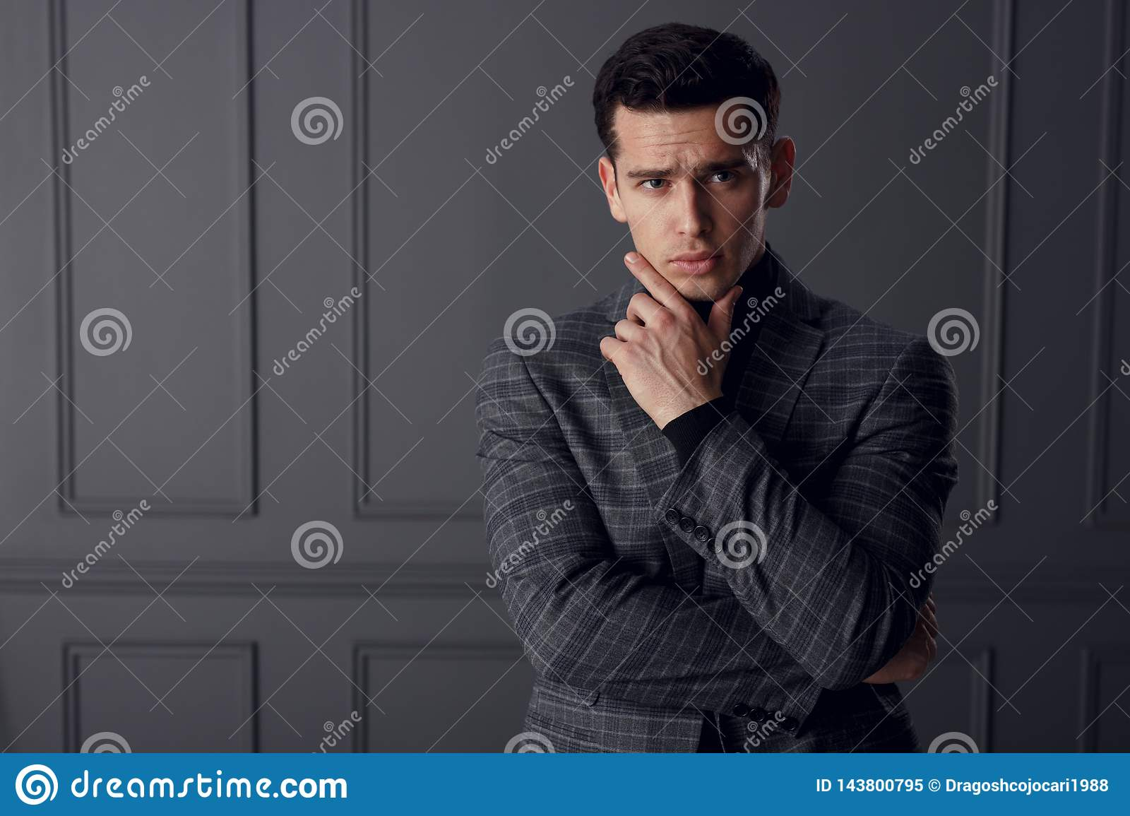 Portrait of handsome young man wear in plaid jacket posing in the position of businessman,  on gray background.