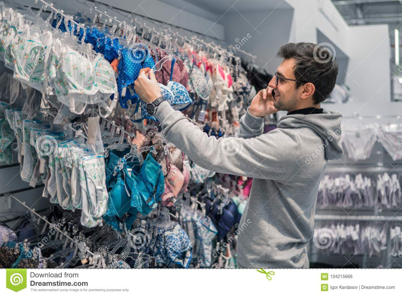6c32e70bb96 Portrait of happy adult man choosing lingerie underwear for his wife in  supermarket shop. He is taking advice by mobile phone from his wife or  girlfriend.