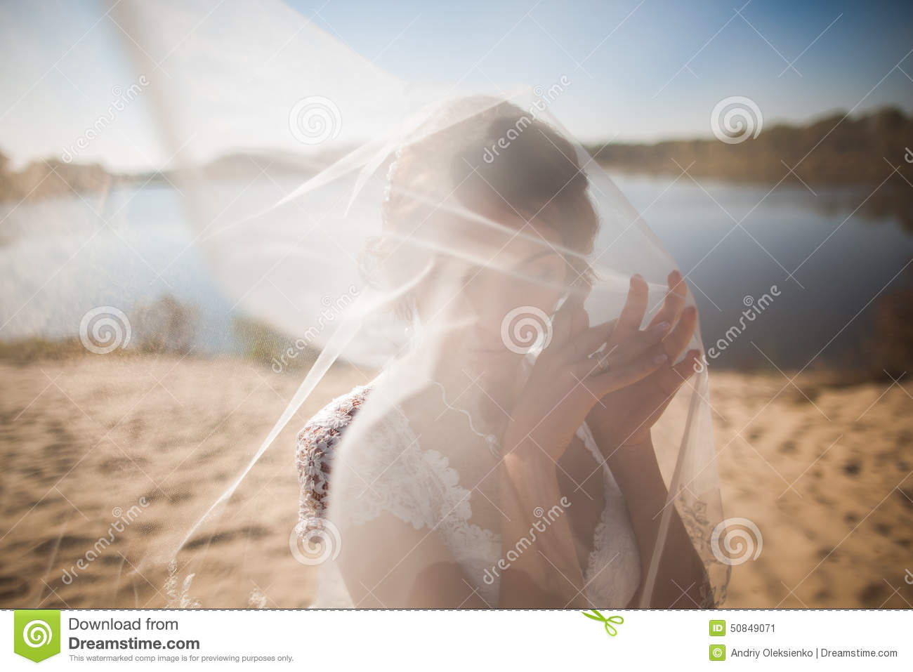 Portrait of happy beautiful bride with head covered bridalveil, standing on beach in wedding day