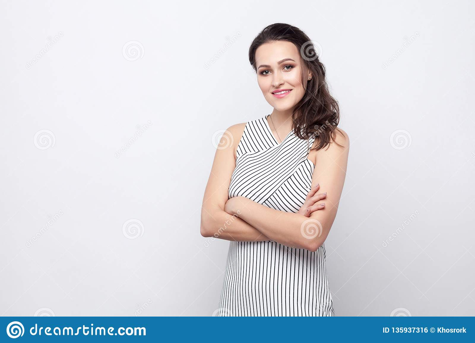 Portrait of happy beautiful young brunette woman with makeup and striped dress standing with crossed arms and looking at camera