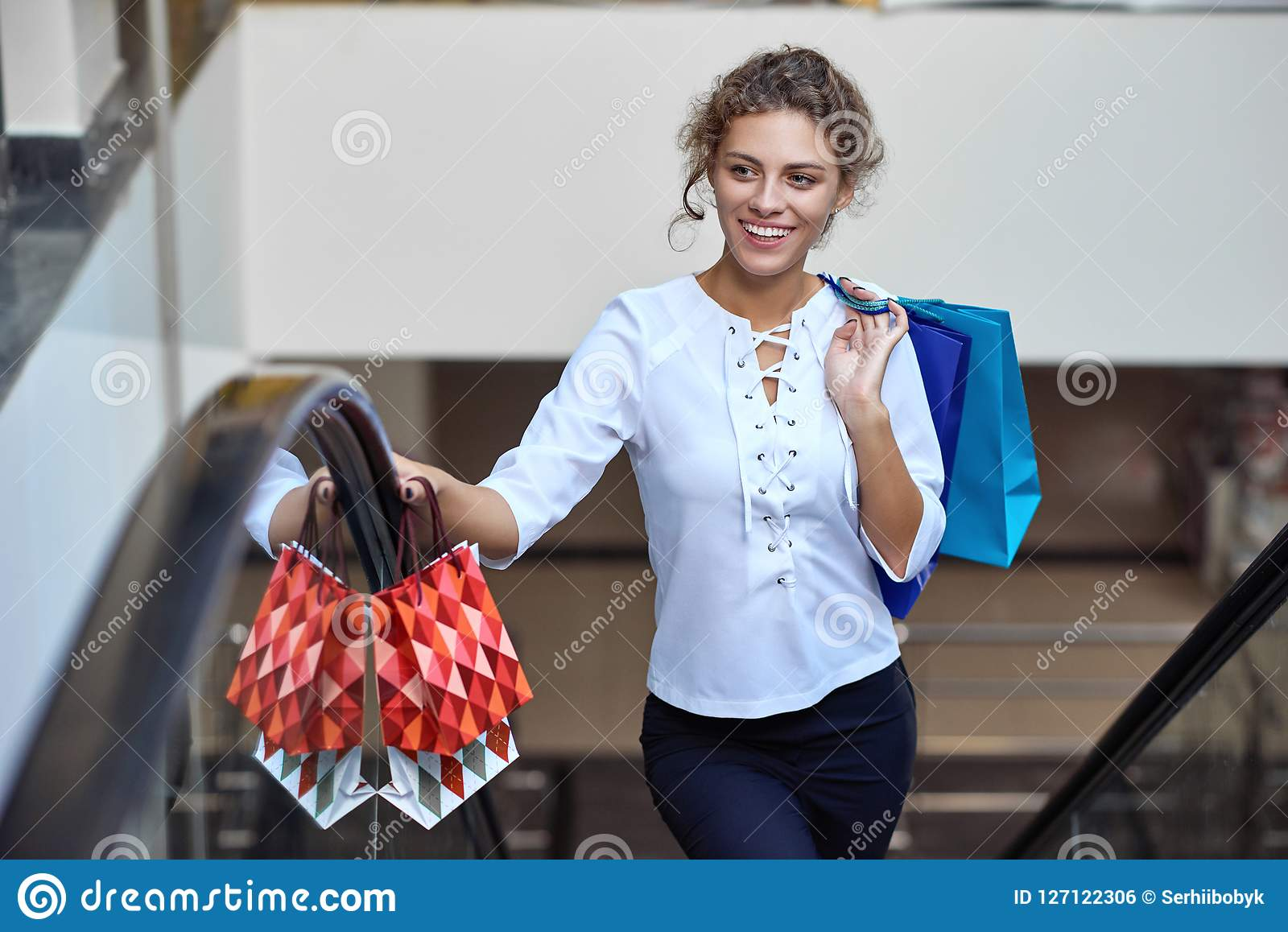 a04f5693 Portrait of happy blonde after good shopping driving up on escalator in mall.  Beautiful woman with shopping bags and purchases smiling and looking away.
