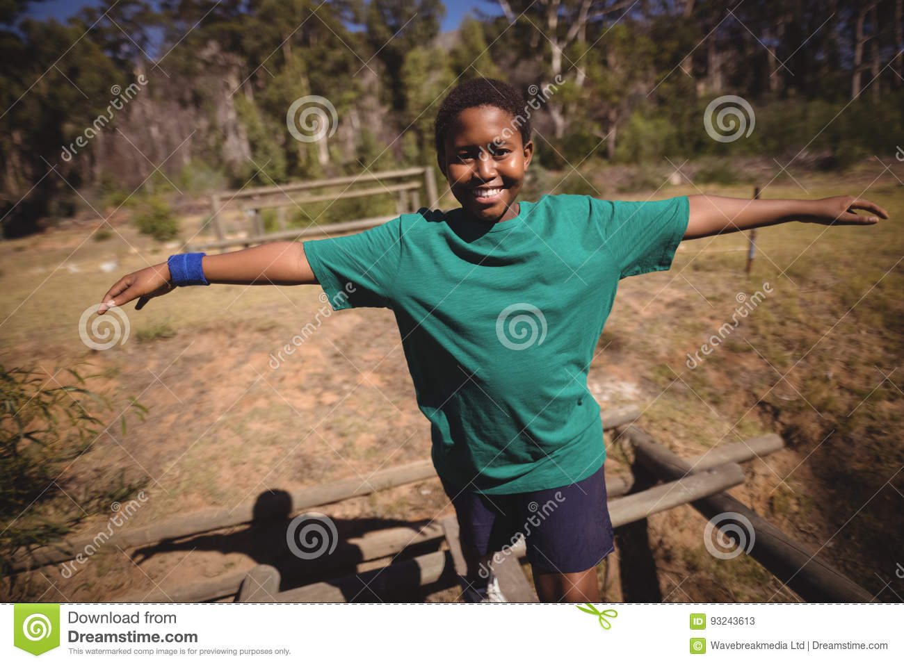 Portrait of happy boy walking on obstacle during obstacle course