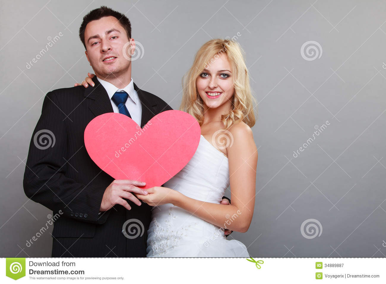 Wedding day. Happy blonde bride and groom holding red heart symbol ...
