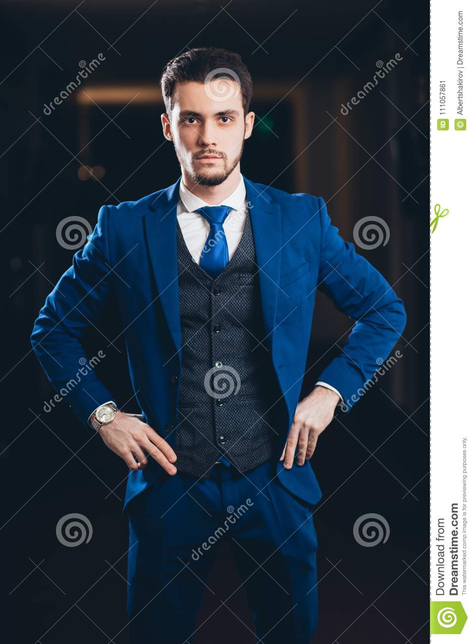 Happy businessman with arms crossed standing in office