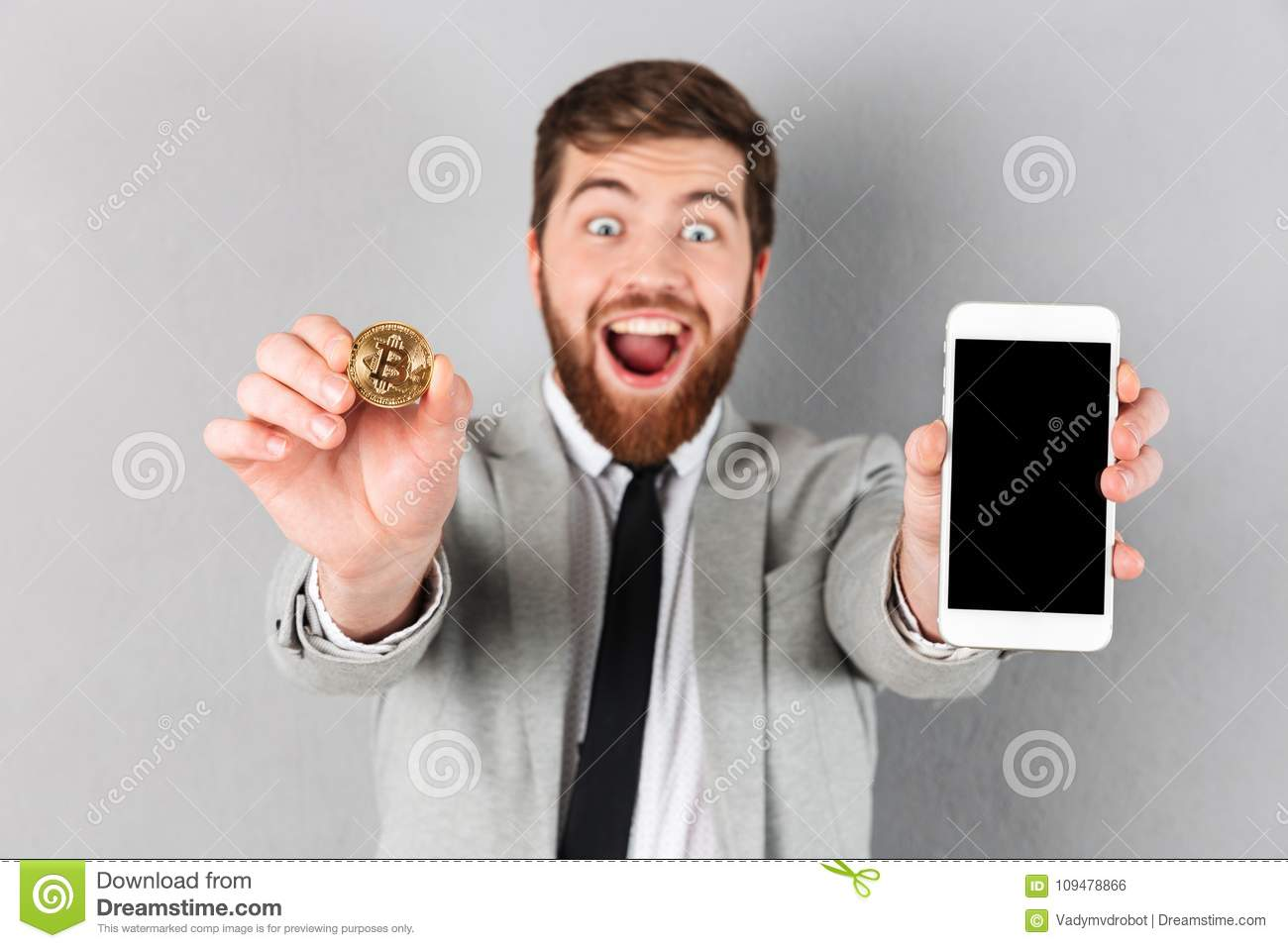 Portrait of a happy businessman holding bitcoin