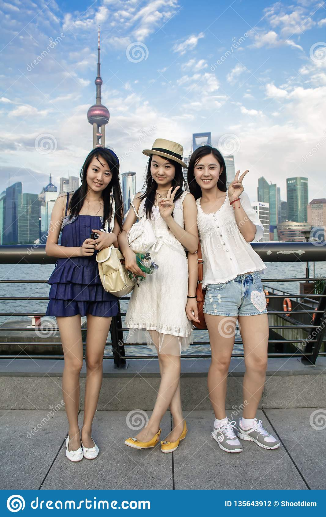 Portrait of Happy chinese young women smiling with modern urban skyscrapers at background