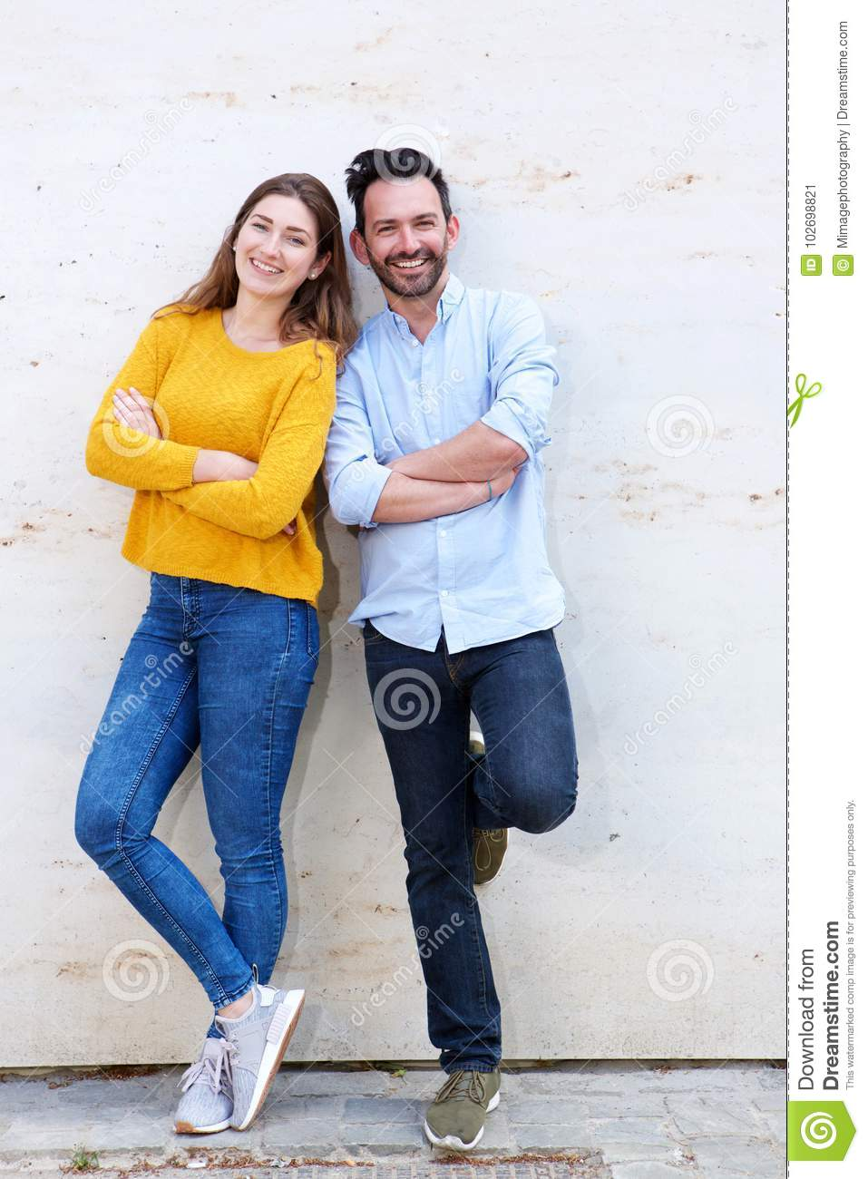 Portrait Of Happy Couple Posing Together Standing With Arms