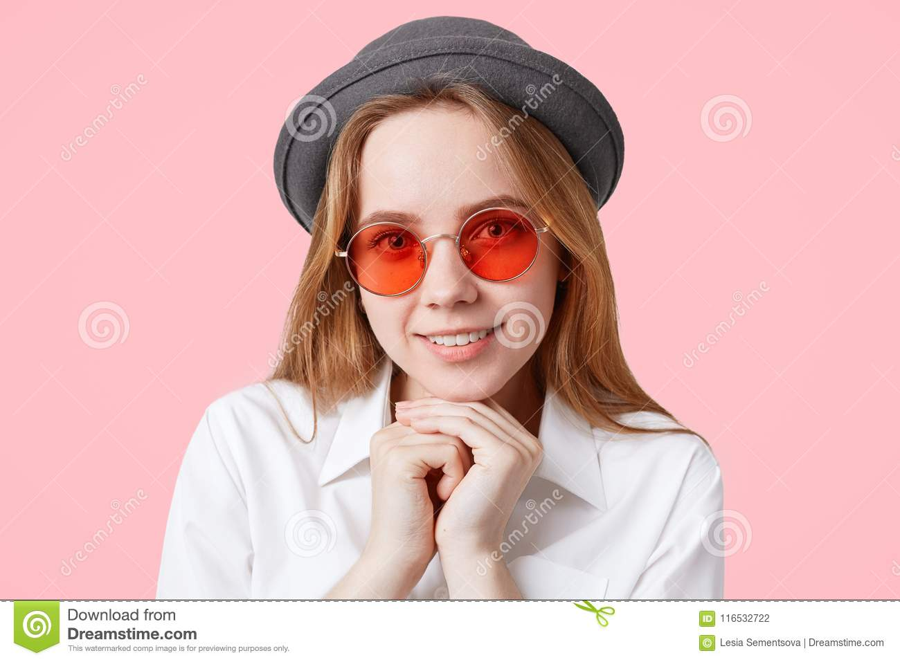 Portrait of happy delighted female model in round red sunglasses and elegant hat, keeps hands under chin, smiles broadly, isolated