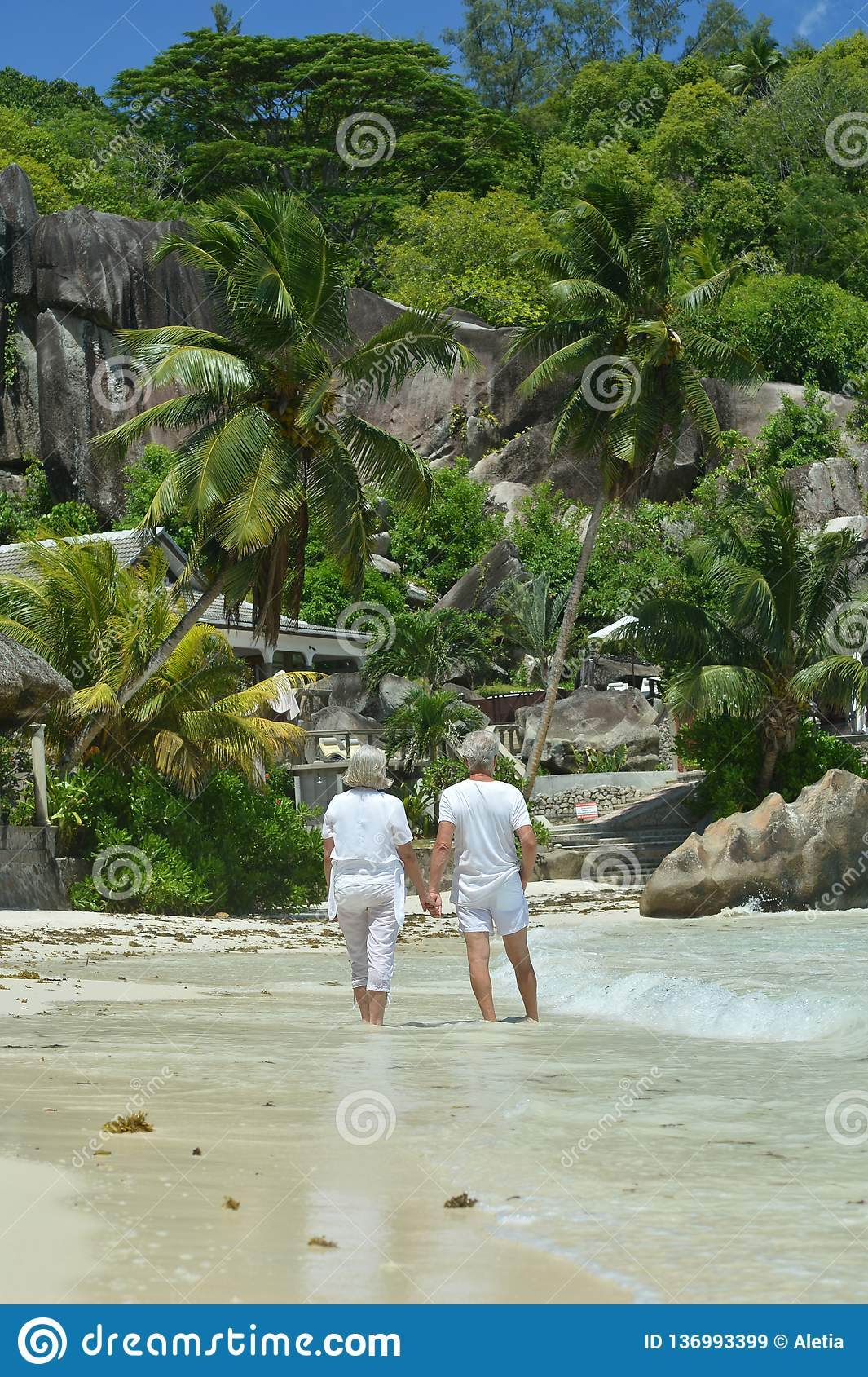 Portrait of happy elderly couple walking on tropical beach. Happy elderly couple walking on tropical beach royalty free stock images