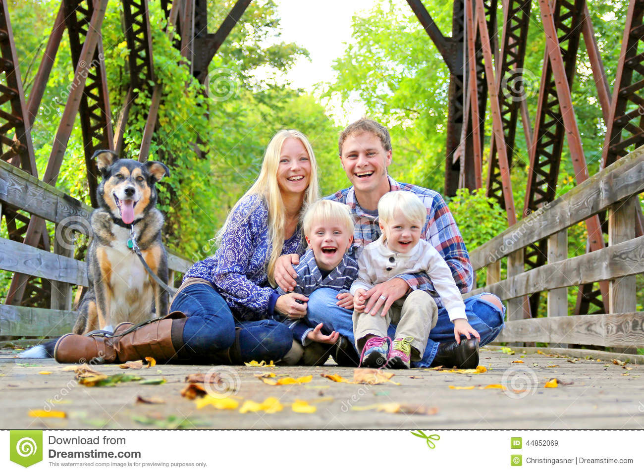 portrait of happy family and dog outside in fall stock photo