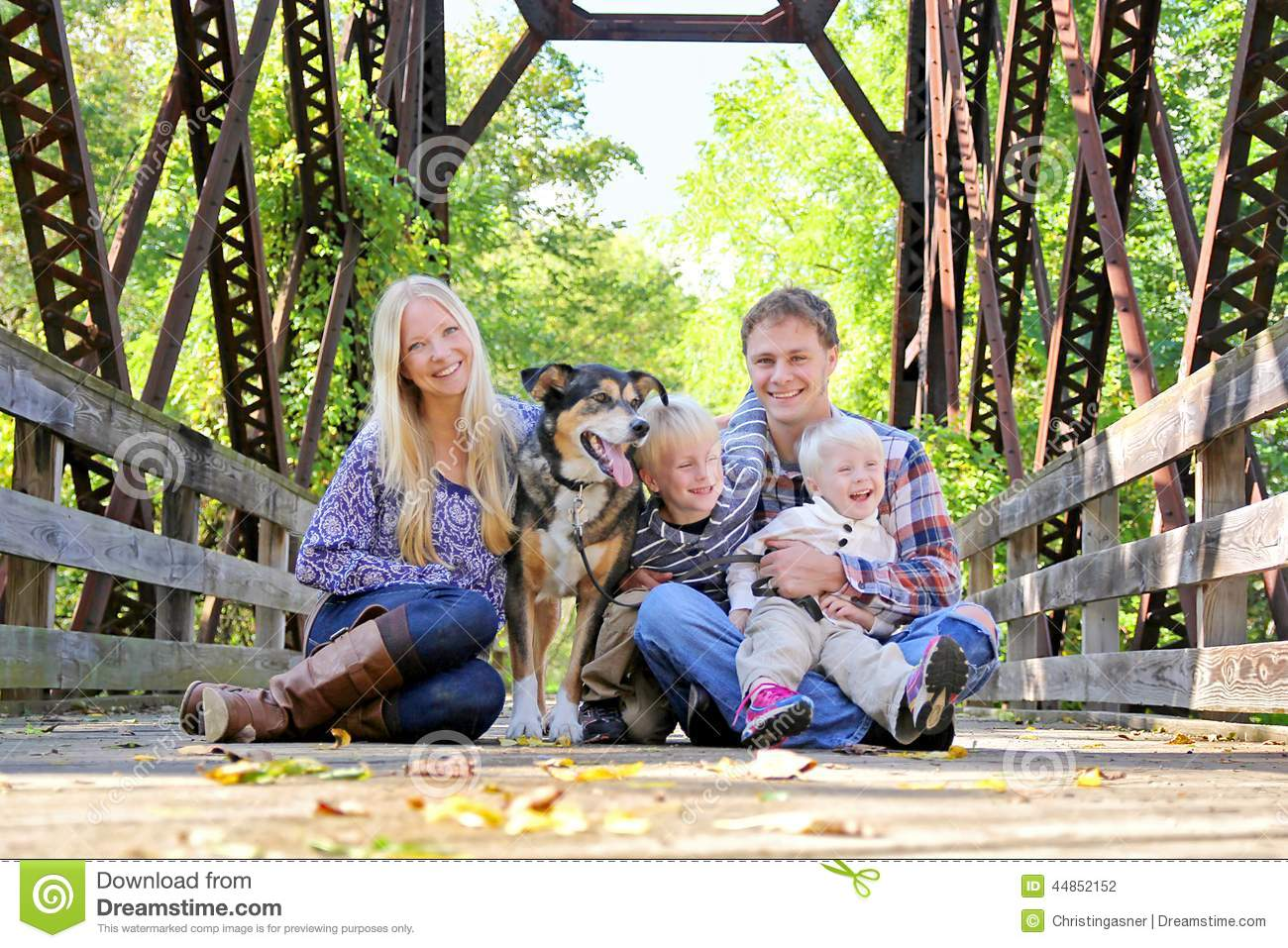 Portrait Of Happy Family And Dog Sitting On Bridge In Autumn Woo