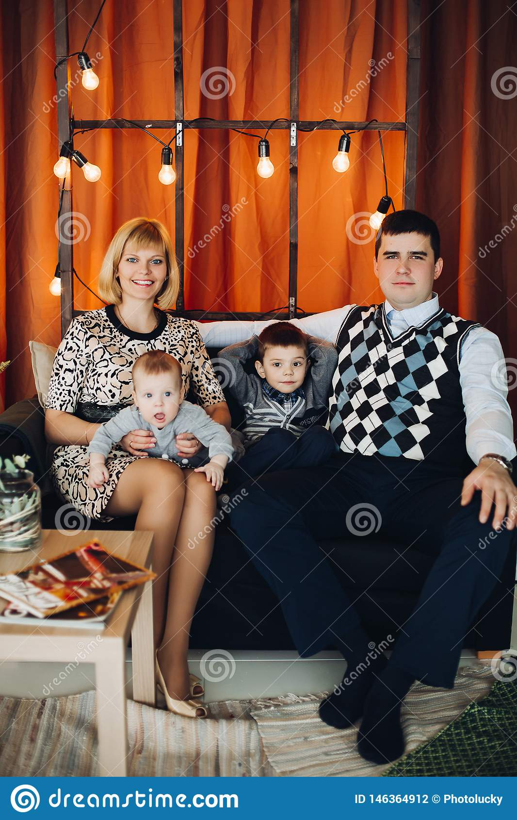 Portrait of happy family embracing in decorated studio.